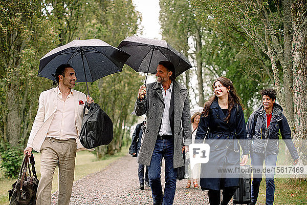 Smiling businessmen and businesswomen walking with luggage on footpath