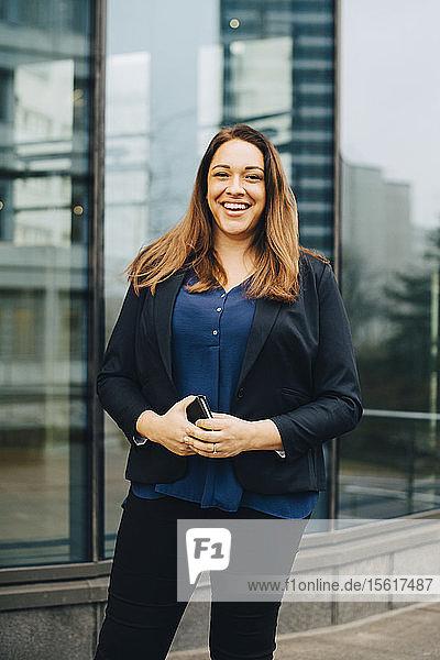 Lächelnde Geschäftsfrau hält Mobiltelefon in der Hand  während sie sich gegen ein Büro stellt