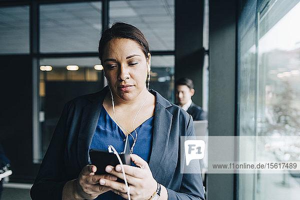 Geschäftsfrau benutzt Smartphone  während sie im Büro über Kopfhörer hört