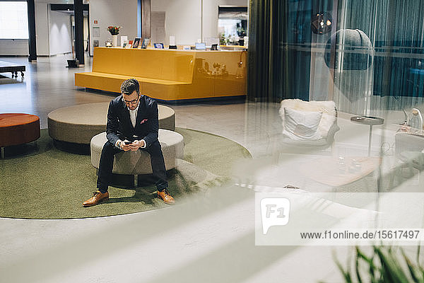 Full length of businessman using mobile phone while sitting in lobby at office