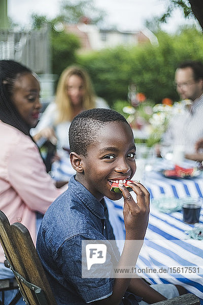 Smiling boy eating watermelon while sitting with family at table in garden