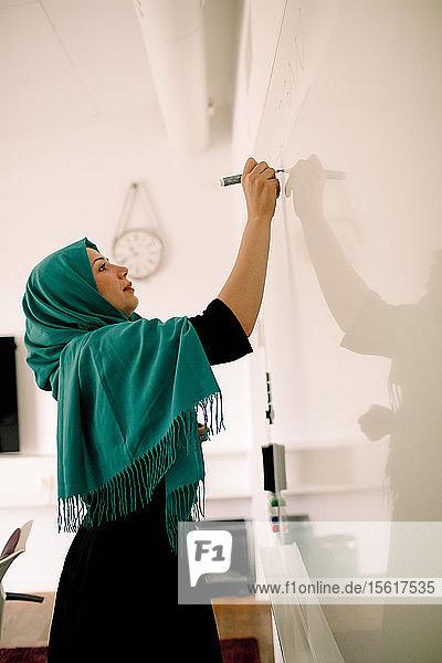Seitenansicht einer Geschäftsfrau in Hijab-Schrift an der Tafel im Kongresszentrum