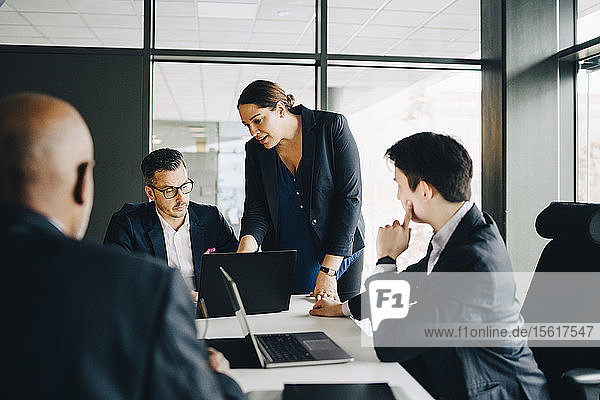 Businesswoman discussing over laptop with colleagues in conference room at office