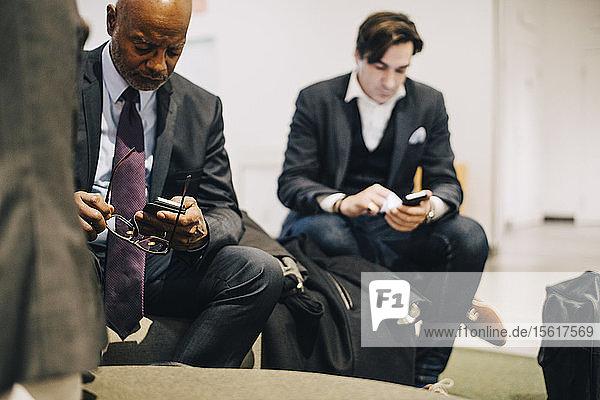 Geschäftsleute benutzen Mobiltelefone  während sie im Büro sitzen