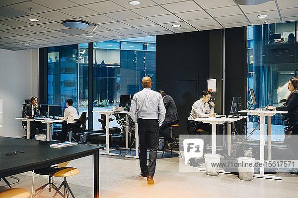 Manager auf dem Weg zu Geschäftsleuten  die am Schreibtisch im Büro arbeiten