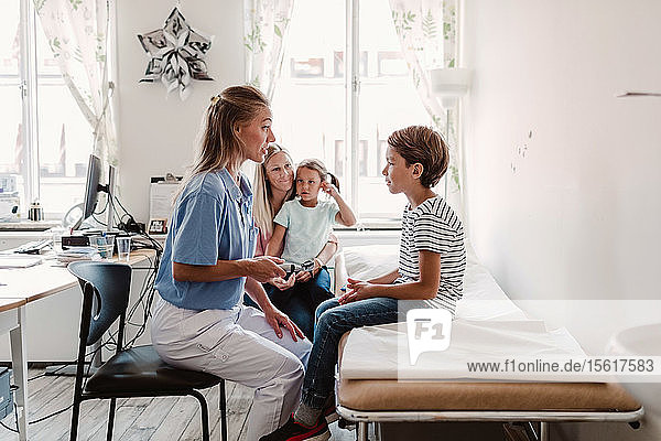 Female pediatrician with otoscope examining boy while family sitting in background at clinic