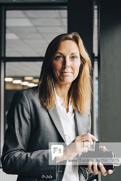 Porträt einer lächelnden Geschäftsfrau mit Smartphone im Büro