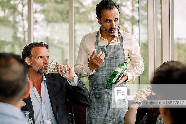 Geschäftsmann mit Weinflasche erklärt Kollegen im Kongresszentrum