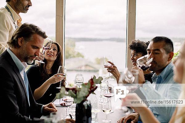 Männliche und weibliche Kollegen mit Rotwein am Tisch während des Auftakttreffens im Kongresszentrum