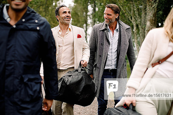 Lächelnde männliche Berufstätige  die während einer Geschäftsreise mit Kollegen gehen