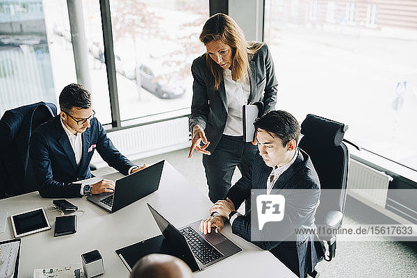 Businesswoman discussing with coworker over laptop while professional working at conference table in corporate office