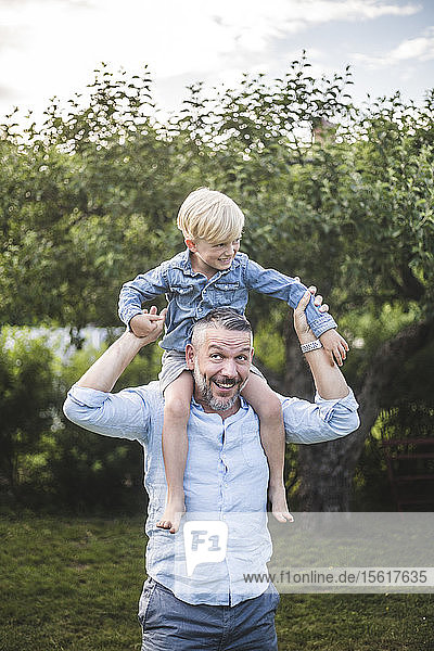Vater trägt Sohn auf den Schultern im Hof und genießt Sommerwochenende