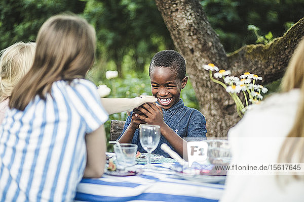Smiling boy looking at phone while sitting with friends at dining table in backyard