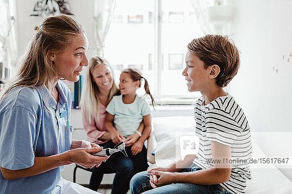 Lächelnde Kinderärztin mit Otoskop im Gespräch mit dem Jungen  während die Familie im Hintergrund in der medizinischen Klinik sitzt