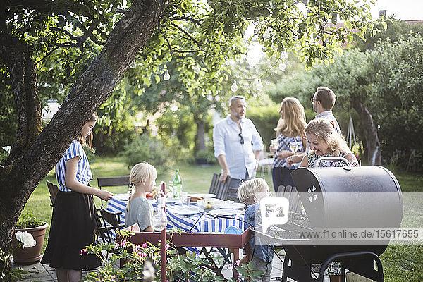 Junge bereitet mit der Mutter auf dem Grill Essen vor  während die Familie am Esstisch im Garten feiert