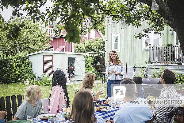 Glückliche Frau hält Rede  während sie während einer Gartenparty mit Freunden bei Tisch anstößt