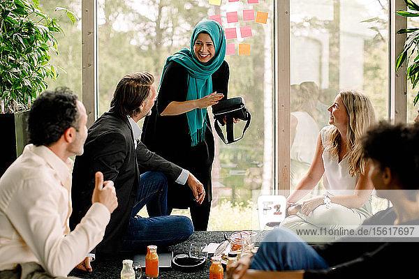 Lächelnde Geschäftsfrau diskutiert mit männlichen und weiblichen Kollegen während eines Treffens im Kongresszentrum