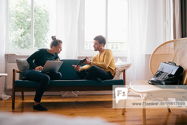 Boyfriend showing digital tablet to girlfriend while sitting on sofa at home