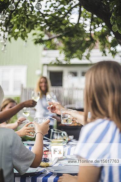 Kinder stoßen auf Trinkgläser an  während sie mit der Familie am Esstisch im Garten sitzen