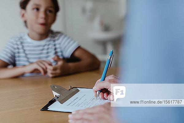 Geschnittene Hände eines Arztes  der ein Rezept schreibt  während ein Junge in der Klinik am Schreibtisch sitzt