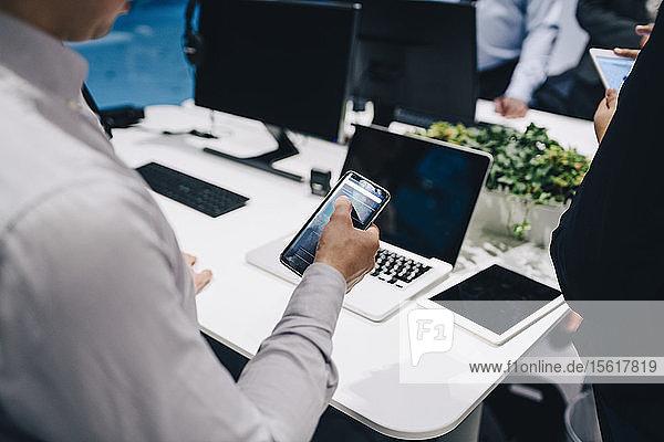 Mittelteil eines Geschäftsmannes  der ein Smartphone am Büroschreibtisch benutzt