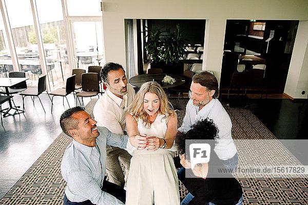 Verspielte Geschäftsleute und Geschäftsfrau heben eine Kollegin im Kongresszentrum
