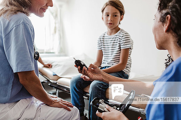 Weibliche Gesundheitshelferin und Kinderärztin zeigt Glaukometer einem Jungen  der im Behandlungszimmer sitzt