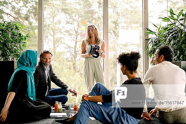 Lächelnde Geschäftsfrau hält Virtual-Reality-Simulator in der Hand  während sie mit Kollegen im Kongresszentrum diskutiert