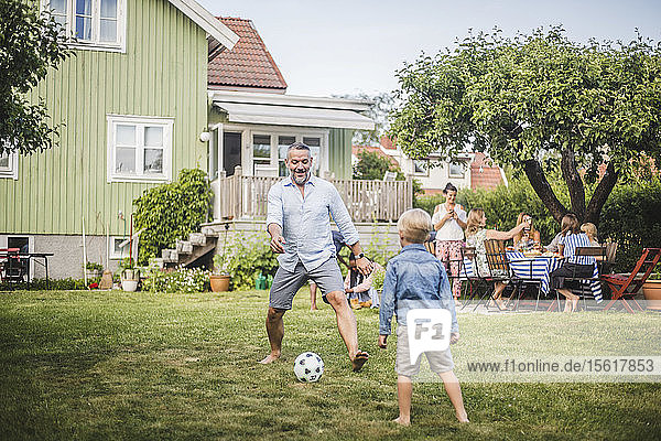 Father playing football with son while friends having fun at table in backyard party