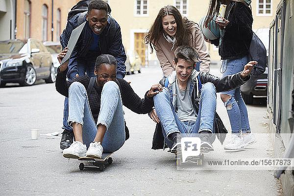 Fröhliche Freunde schubsen Teenager  die auf Skateboard sitzen