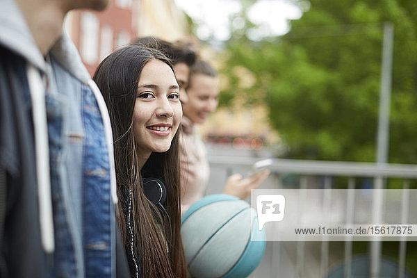 Porträt eines lächelnden Teenagers  der mit Freunden spazieren geht