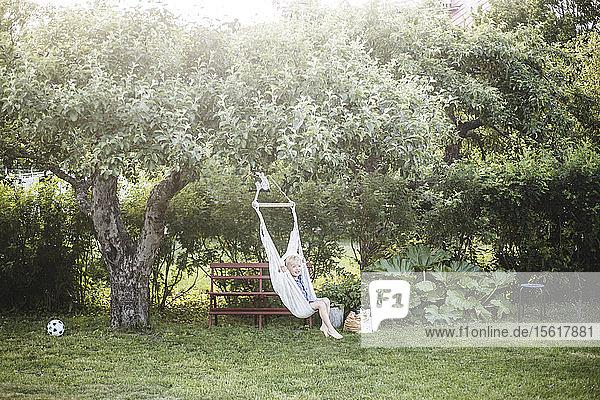 Junge schwingt am Sommerwochenende in voller Länge im Hinterhof