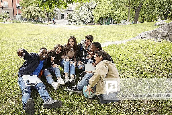 Schrägaufnahme von fröhlichen Freunden  die im Park sitzen