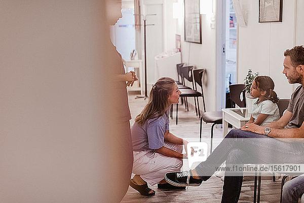Weibliche Kinderärztin im Gespräch mit Patientin auf dem Krankenhauskorridor