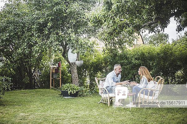 Paar redet in voller Länge  während es im Hinterhof sitzt