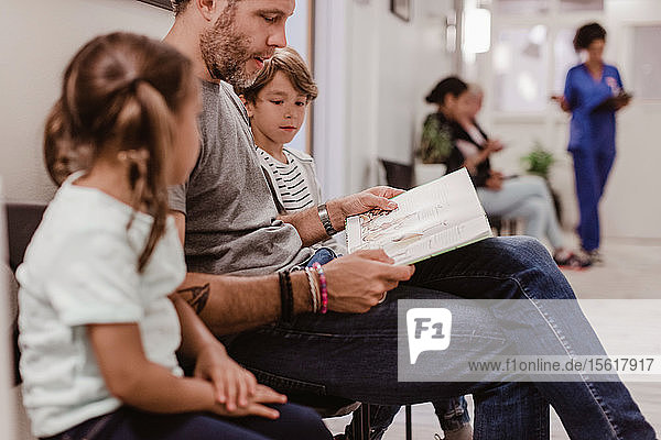 Father reading book for son and daughter while waiting in hospital corridor