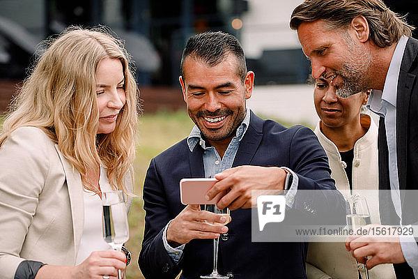 Lächelnder Geschäftsmann zeigt männlichen und weiblichen Kollegen sein Handy  während er eine Sektflöte hält