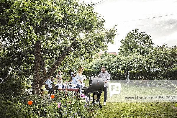Männliche und weibliche Freunde bereiten das Essen auf dem Grill zu  während die Familie im Hinterhof Spaß hat