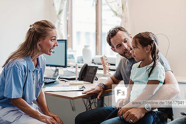Ärztin im Gespräch mit einem Mädchen  das mit seinem Vater in einer medizinischen Klinik sitzt