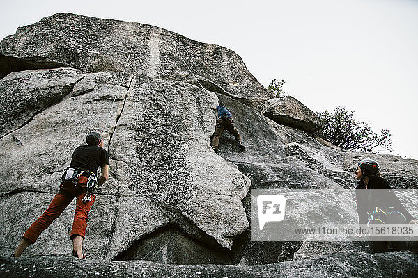 Climbers on Penthouse Cracks (5.8) at the Swan Slab wall in Yosemite Valley.