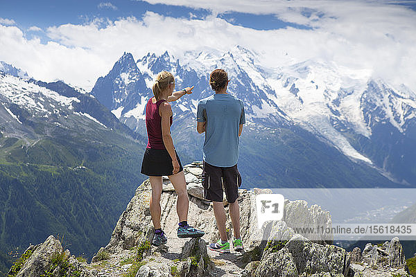 Two runners are standing on top of a mountain  overlooking the Chamonix valley and Mont Blanc range. This region in the French Alps is popular for trail running or sky running.