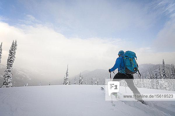 Man Skiing Across A Snow Covered Mountain Ridge