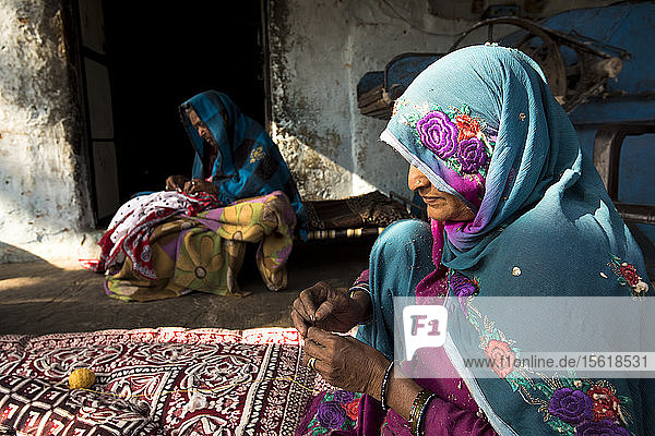 Two Indian woman in colorful clothing make blankets in Jaipur  India.