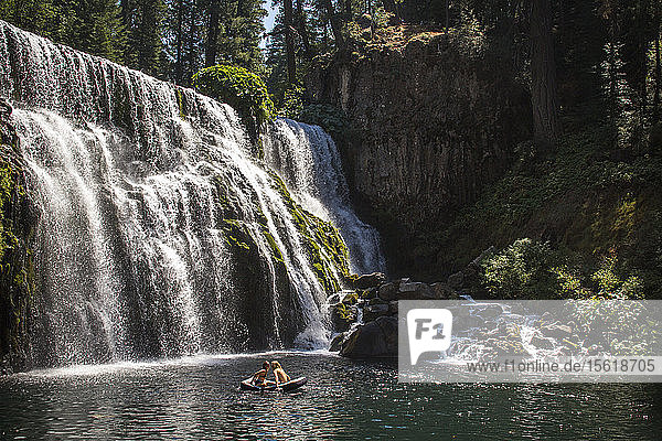 Distant view of couple in raft floating on water near waterfall  ï¾McCloudï¾River  California  USA