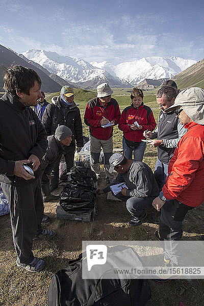 A group of mountaineers negotiating the price for the porters at basecamp of Lenin peak (Kyrgyzstan).