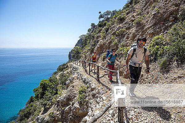 A boy and two girls hiking the first section of Selvaggio Blu  a 6 days hike that is supposed to be the hardest trail in Europe because of the lack of water  some climbign and rapelling sections and because is often difficult to find the trail. Sardinia  Italy.