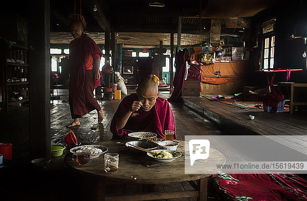 Young monk eating at table in rural monastery with another monk walking behind in background  Myanmar  Shan  Myanmar