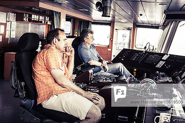 Captain and first officer sitting at the navigation deck onboard a container ship.
