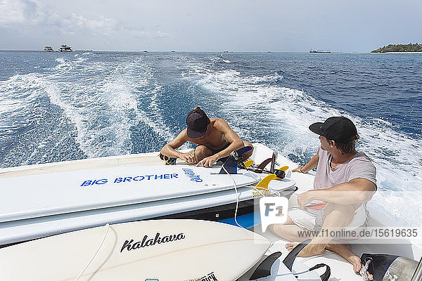 Two young men sitting on moving motorboat transporting surfboards  Male  Maldives