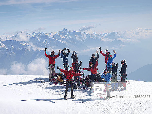 A group of young people are waiving while standing on a mountain top. They reached the summit of the Bishorn during a junior mountaineering course in the Swiss Alps.